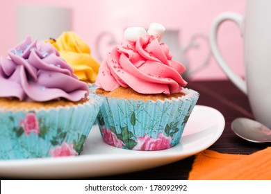 various cupcakes on a plate on pink background