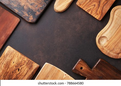 Various cutting boards on stone table. Cooking utensils. Top view with space for your text