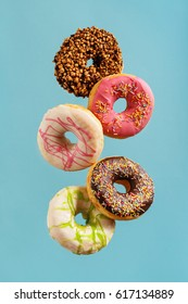 Various decorated doughnuts in motion falling on blue background. Sweet and colourful doughnuts falling or flying in motion.