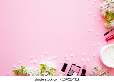 Various decorative makeup cosmetics with herbal cream jar and fresh cherry blossoms  and petals on pink pastel desk. Mockup for special offers as advertising. Empty place for text. Flat lay. Top view.