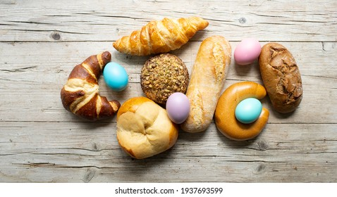 various delicious and fresh Easter pastries and colorful Easter eggs on light wooden background photo taken from above