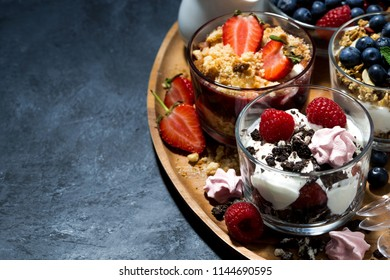 various desserts with berries and cream on dark background, top view, horizontal