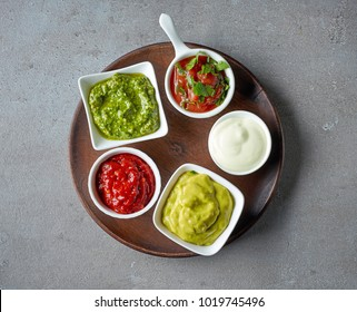 various dip sauces on grey table, top view