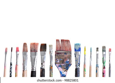 Various dirty paint brushes displayed side by side with copy-space to the top.