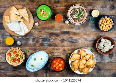 Various dishes of Pakistani and Bangladeshi cuisine on a wooden table Banner. copy space. concept: Eid al-fitr, end of Romadan, a generous treat.