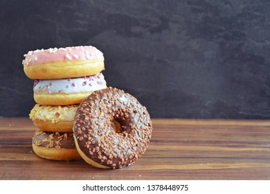 Various donuts with chocolate and nuts are stacked together on a pile with a wooden background and a dark background - concept with donuts and place for text and other elements