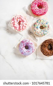 Various donuts on a marble pattern background. Top view shot. Sweetness, happiness conception.