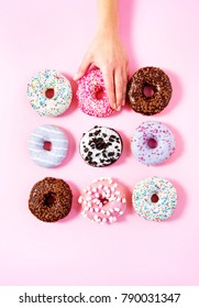 Various donuts on a pink background. A woman's hand taking one. Sweetness happiness conception.