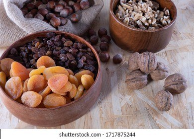 various dried fruits, apricot, nuts and raisins in a wooden cup on a wooden background