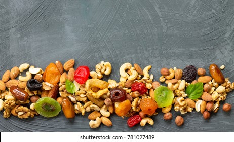 Various dried fruits and mix nuts on a gray stone or slate background.  The concept of the Jewish holiday Tu Bishvat. Flat lay, top view with copy space.