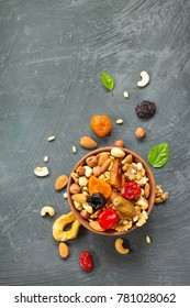 Various dried fruits and nuts in a ceramic bowl (walnut, cashew, almonds, pine nuts, hazelnuts) on a gray stone or slate background. The concept of a healthy dessert. Flat lay, top view.