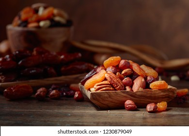 Various dried fruits and nuts on a old wooden table.