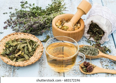 Various dried meadow herbs and herbal tea on light old wooden table. Dried medicinal plants in bag, basket, mortar and in bundle. Preparing medicinal plants for phytotherapy and health promotion