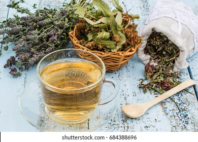 Various dried meadow herbs and herbal tea on light old wooden table. Dried medicinal plants in bag, basket and in bundle. Preparing medicinal plants for phytotherapy and health promotion