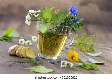 Various dried meadow herbs and herbal tea on old wooden table. fresh medicinal plants and in bundle. Preparing medicinal plants for health promotion