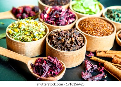Various dried tea leaves in wooden bowl. Dried herbs tea leaves close up. Different dry herbs and flowers for making healthy tea background.