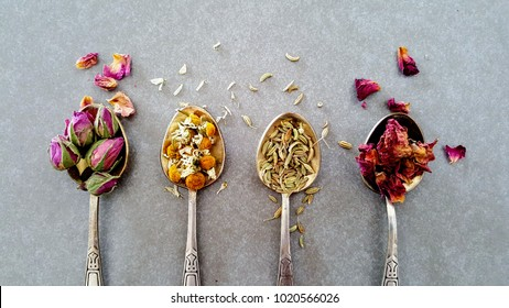 Various dry herbs and spices in vintage silver teaspoons. Flat lay of Indian Crumbled Roses, Fennel Seeds, Chamomile and Moroccan Roses on gray background.