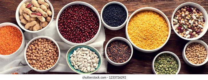 Various dry legumes on wooden board. Top view. Panorama