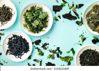 Various dry seaweed, sea vegetables, shot from the top on a teal background forming a frame for copy space