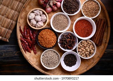 Various dry spices and herbs in a bowl on bamboo tray. Asian food ingredients (chili, clove, caraway, coriander seed, star anise, cardamom, pepper, cinnamon, garlic and shallot)