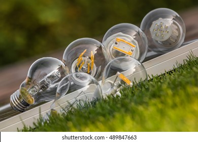 various E27 bulbs, LED, halogen and tungsten bulb on solar panel, some on the grass ( selective focus )
