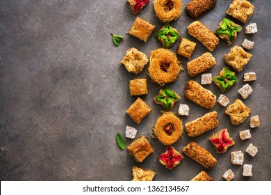 Various Eastern sweets on a rustic brown background. Baklava, delight, cookies. Top view, copy space