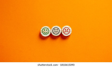 Various emoticons made of wooden circles drawn lines of a mouth. Over orange background in a conceptual image of quality and feedback.