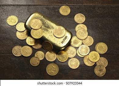 various European circulation gold coins from the 19th/20th century around a gold bar on rustic wooden background