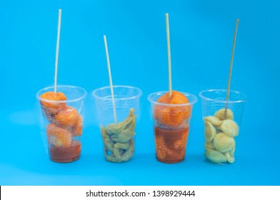 A various Filipino street foods on a plastic cup with sticks on blue isolated background. Philippines street foods and their names such as Kwek - Kwek, Fishball, and Kikiam.