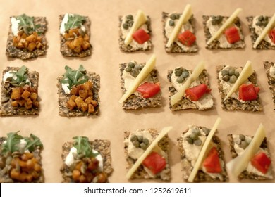 Various finger sandwiches assembled on a parchment paper. Selective focus.