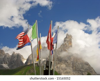 various flags in front of mountain peaks