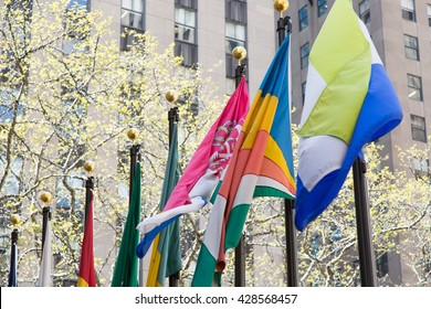 Various flags on a flagpoles on the street