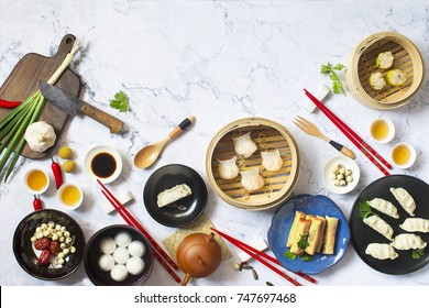 Various flat lay Chinese food, dim sum and tea on marble top.