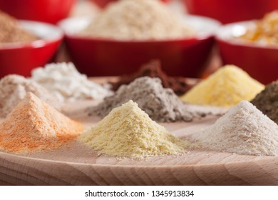 Various flours of a diverse selection of grains and cereals - focus on flour heaps of orange lentils, yellow millet and white rice, macro close up