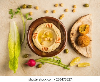 Various food ingredients arranged around bowl of Houmous - a popular Middle Eastern dip. View from top.