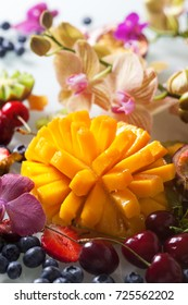 Various fresh fruits and berries with Orchid flower closeup.
