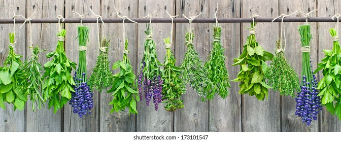 Various fresh herbs hanging in bundle on an iron rod in front of a hut