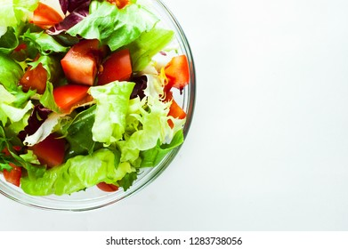 various fresh mix salad leaves with tomato in glass bowl isolated on white background.