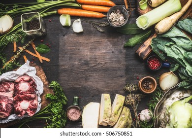 Various Fresh organic ingredients for Broth or soup cooking with vegetables and meat on dark wooden background, top view, frame