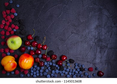 Various fresh summer berries. Mix of fruits and berries on black background. Fruit banner. Selection of healthy vegetarian food, detox or diet concept, space for text. Top view, overhead