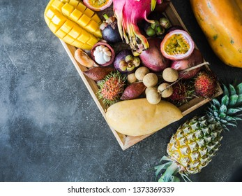 Various fresh Thai fruits - rambutan, mango, mangosteen, longan, papaya, dragon fruit, sapodilla, passion fruit, salak, pineapple on a wooden tray and a gray background. Top view. Copy space