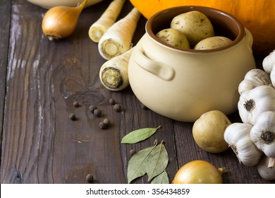 Various fresh vegetables and ceramic pot on old wooden background. Cooking, healthy or vegetarian eating concept.