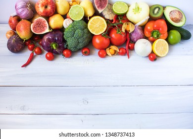 Various fresh vegetables and fruits on a wooden background, top view, copy space. Vegetarian food.