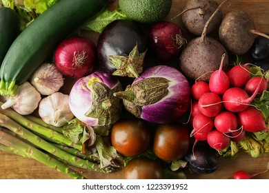 Various fresh vegetables with plums on wooden table
