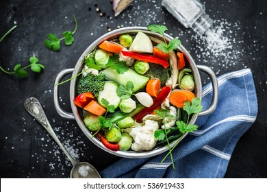 Various fresh vegetables in a pot - colorful fresh clear spring soup (vegetarian bouillon or stock). Cooking - kitchen scenery from above (top view). Black chalkboard background.