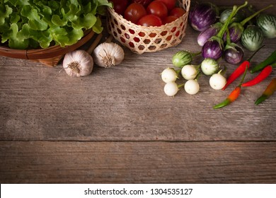 Various fresh, young homegrown vegetables, tomato, chilli,  lettuce, Eggplant, garlic place on a wooden table
