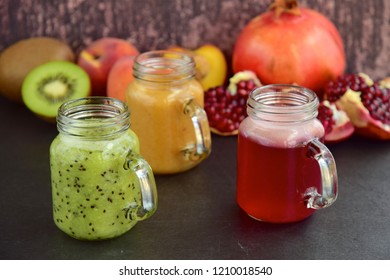 Various freshly squeezed fruit juices in jars on wooden background