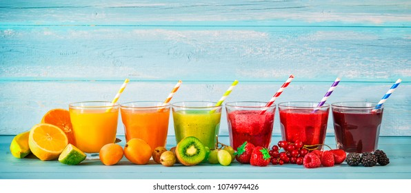 Various freshly squeezed fruits juices on blue wooden background