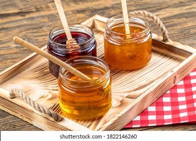 Various fruit marmalade jams in jars top view. Honey, apricot jam and strawberry jam in jars.
