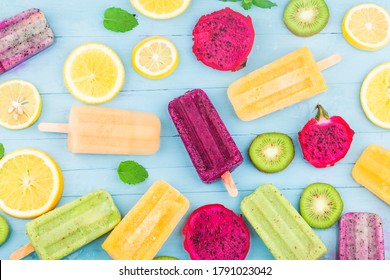Various fruit popsicles are placed on the blue wooden board background, kiwi popsicles, orange popsicles, dragon fruit popsicles, cantaloupe popsicle
